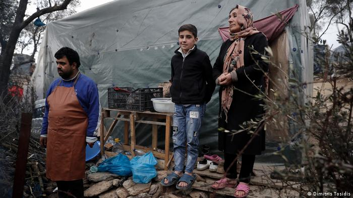 Three refugees in front of their hut (Dimitris Tosidis)
