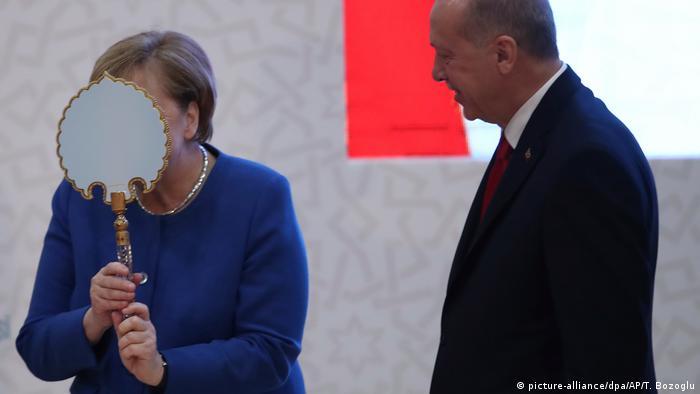 Merkel's face hidden by a mirror standing as she stands next to Erdogan