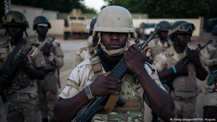 Cameroonian armed forces stand holding guns