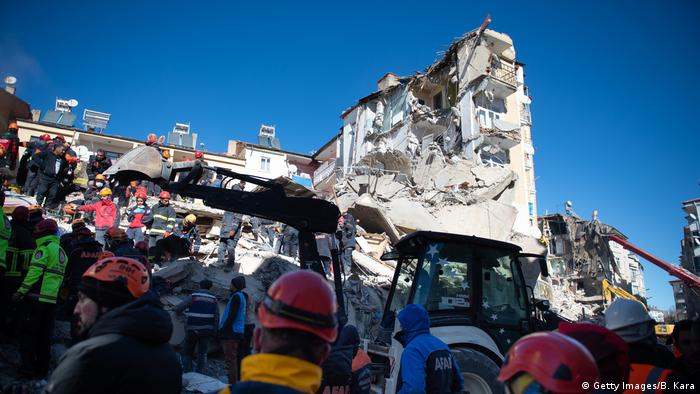 Rescue workers stand before rubble from an earthquake in Elazig