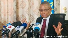 TPLF leader Debretsion Gebremichael stands in front of a bank of microphones