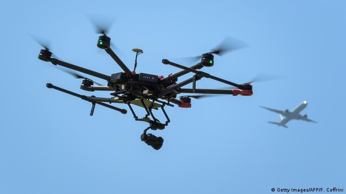 A drone flies as an airplane is seen in the background during a press presentation