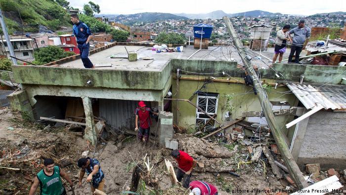 Pessoas avaliam destruição em casa verde, em meio a escombros provocados por deslizamento