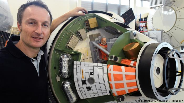 Astronaut Matthias Maurer stands next to a model of the Orion space capsule at the European Astronaut Center