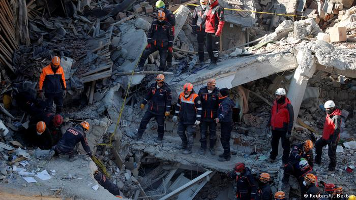 Rescue workers search the site of a collapsed building