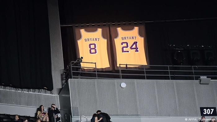 Duas camisetas com os números 8 e 24 projetadas em salão