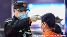 A security personnel checks a passenger's temperature at a subway station in Guangzhou