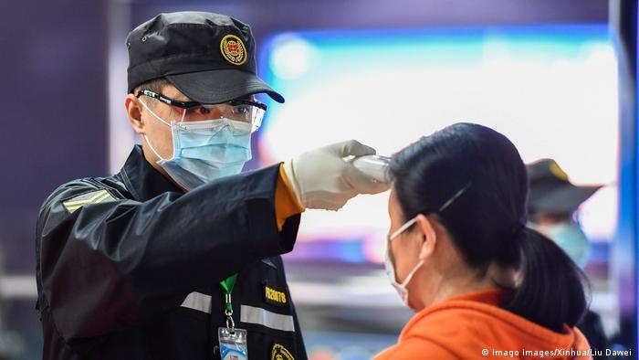 Segurança mede a temperatura de passageira em estação de metrô de Guangzhou, no sul da China