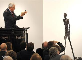Auctioneer Henry Wyndam sells the sculpture Walking Man I at Sotheby's auction rooms in London