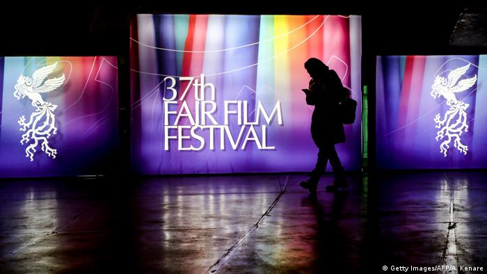 A person walks in front of the screen for the Fajr Film Festival