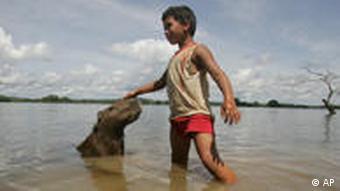 Bedrohtes Idyll? Eine Junge spielt im Xingu mit einem Wasserschwein (AP Photo/Andre Penner)