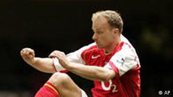 Arsenal's Dennis Bergkamp, right, jumps for the ball against Blackburn's Gary Flitcroft