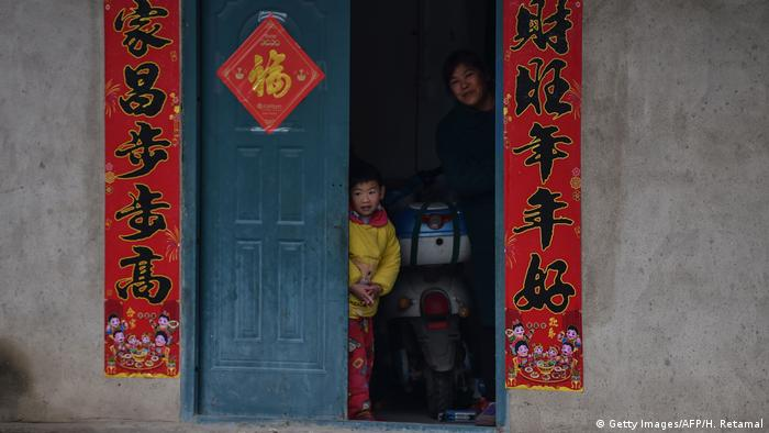 An adult and a child peak through the door of a building in Wuhan