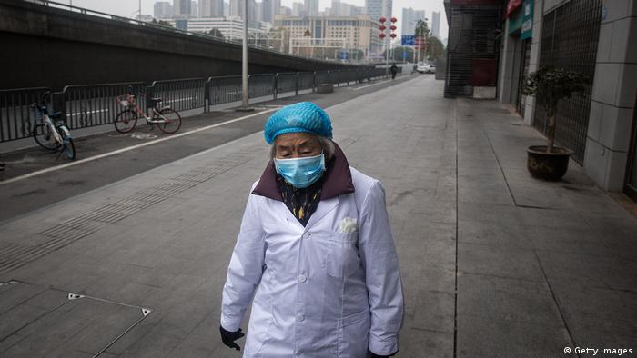 Пожилая китаянка с респираторной маской на лице на пустынной улице города Уханя, ставшего очагом распространения смертоносного коронавируса.