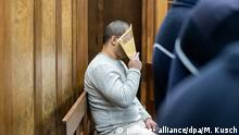 Defendant covering his face with a file (picture- alliance/dpa/M. Kusch)