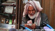 23.05.2018, Jemen, Sanaa: Ein älterer Mann zählt in der Altstadt am Straßenrand Geld. Viele Menschen leiden auch im Fastenmonat Ramadan zunehmend unter den Folgen des seit drei Jahren anhaltenden Bürgerkrieges in dem arabischen Land. Foto: Mohammed Mohammed/XinHua/dpa +++(c) dpa - Bildfunk+++ |