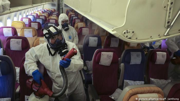 Mitarbeiter von Thai Airways desinfizieren ein Flugzeug, in dem eine Corona-Infektion festgestellt worden war
