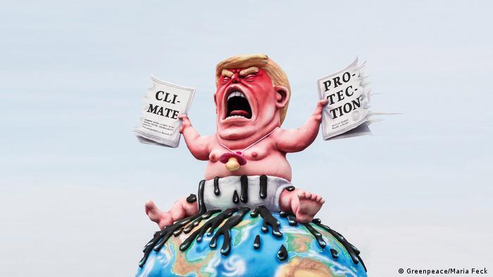 Trump sitzt mit Schnuller um den Hals auf einem Globus. In jeder Hand einen Teil des zerissenen Klimaabkommens. Schloss Oberhausen Ludwiggalerie Ausstellung Jacques Tilly (Greenpeace/Maria Feck )