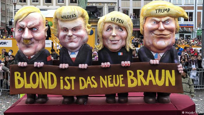 Four figures ( Trump, Le Pen, Wilders und Adolf Hitler.) with blond hair and a large banner that reads blond is thre new brown Schloss Oberhausen Ludwiggalerie Ausstellung Jacques Tilly (Hojabr Riahi)