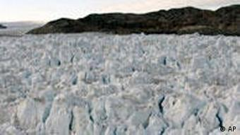 Researchers with tracking equipment examine a glacier in Greenland.