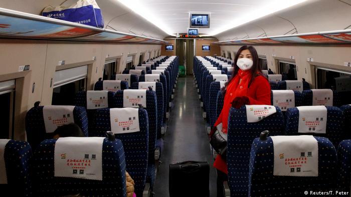 Una mujer tiene una mascarilla al interior de un avión comercial.