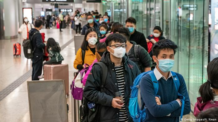 Viajantes de máscara esperam em fila em aeroporto de Hong Kong