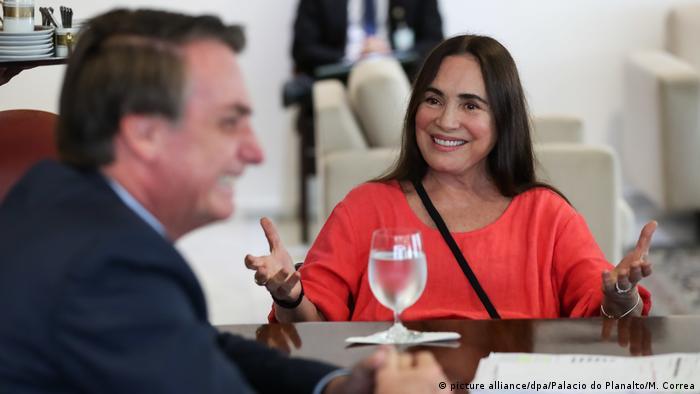 Regina Duarte sentada numa mesa diante de uma taça de água. À frente dela, desfocado, Jair Bolsonaro de perfil