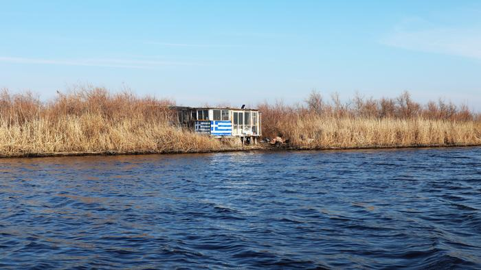 A hut on the Evros river with a Greek flag