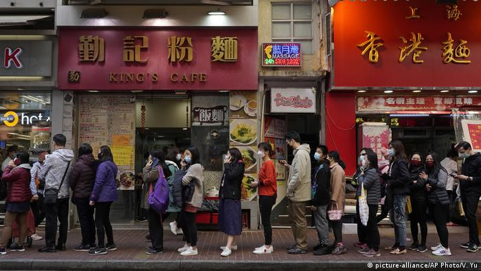 People queue up to buy face masks at a cosmetics shop in Hong Kong