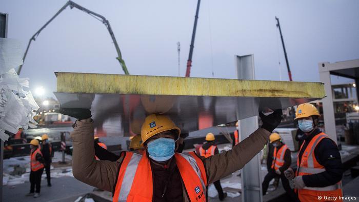Рабочий держит над головой строительную плиту