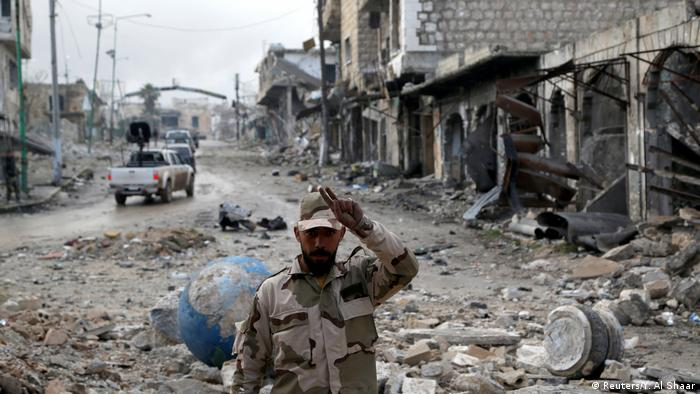 A Syrian soldier amid destroyed buildings