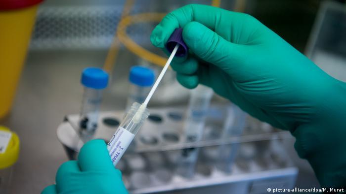 Тест на коронавирус: руки в медицинских перчатках и пробирка