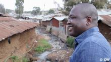 Kennedy Odede in profile, wearing a blue shirt, smiling and with Kibera slum in the background. (DW)