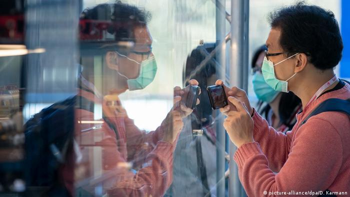 Asistente al evento utiliza una mascarilla para prevenir contagio del coronavirus.