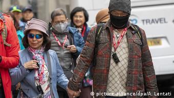 Люди в масках на одной из улиц Лондона