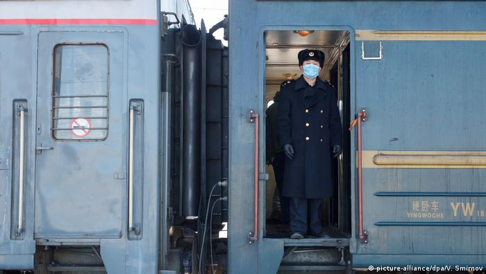 A conductor in a medical face mask stands in the door of a passenger train en route from Beijing to Moscow.