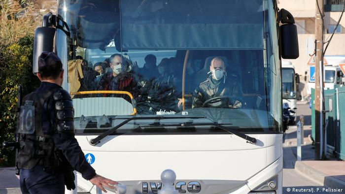 French citizens arriving in France from Wuhan are seen wearing medical face masks inside a bus.