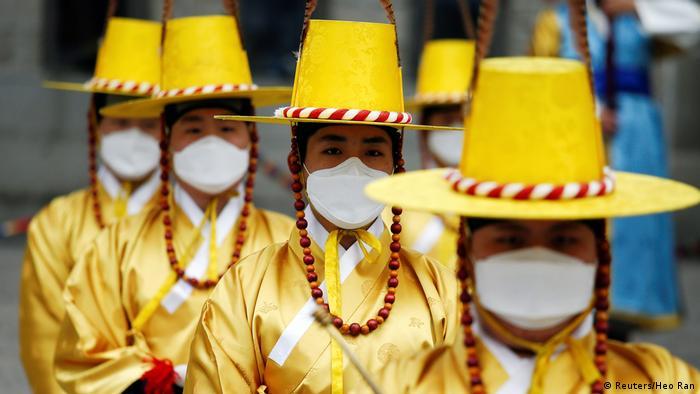 BdTD Südkorea Arbeiterinnen in traditioneller Tracht tragen Schutzmasken (Reuters/Heo Ran)