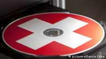 A compact disc with a Swiss flag painted on it rests in an open computer CD tray