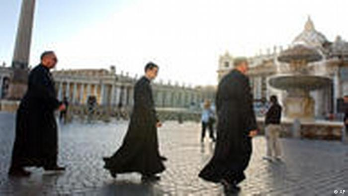 Three priests cross St. Peter's Square at the Vatican