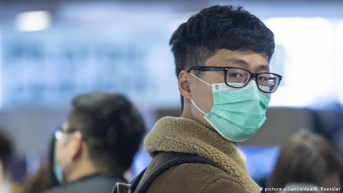 Passenger wearing a face mask at the Air China check-in at Frankfurt Airport