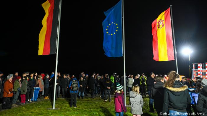 A crowd of people watches the German, European and regional flags at the geographical center in Gadheim