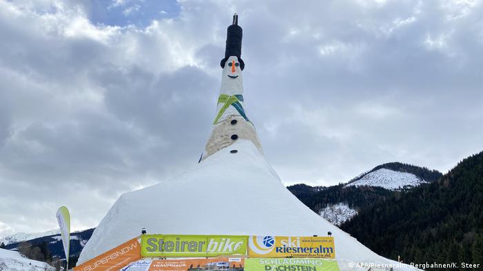 A man stands on the top hat worn by the tallest snowman in the world