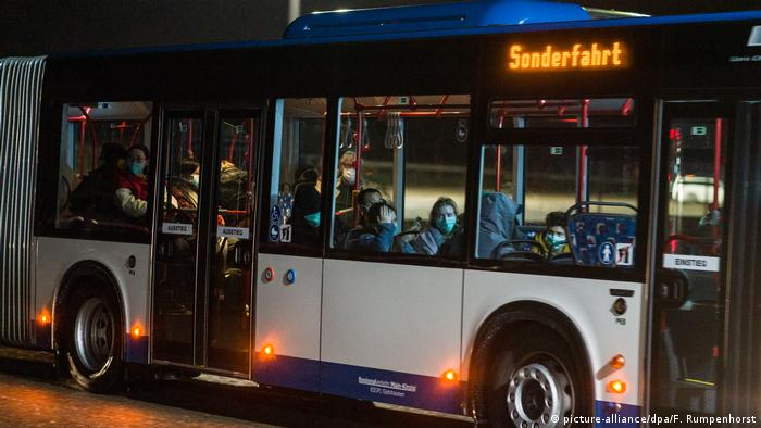 Evacuees arrive in Germersheim on a special chartered bus wearing facemasks