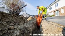 Technik: Digitalisierung, Glasfaser, Glasfaserausbau in Rietberg-Mastholte am 09.04.2019. Ein Arbeiter verlegt Leerrohre im Erdreich.   Verwendung weltweit