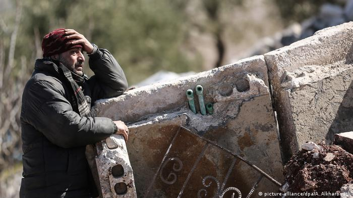 A man cries in the aftermath of an aerial bombing in Idlib, Syria