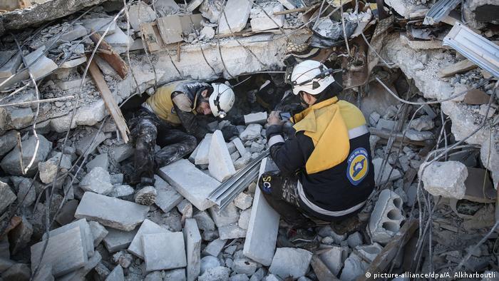 Zwei Männer mit weißen Helmen in den Trümmern eines Gebäudes