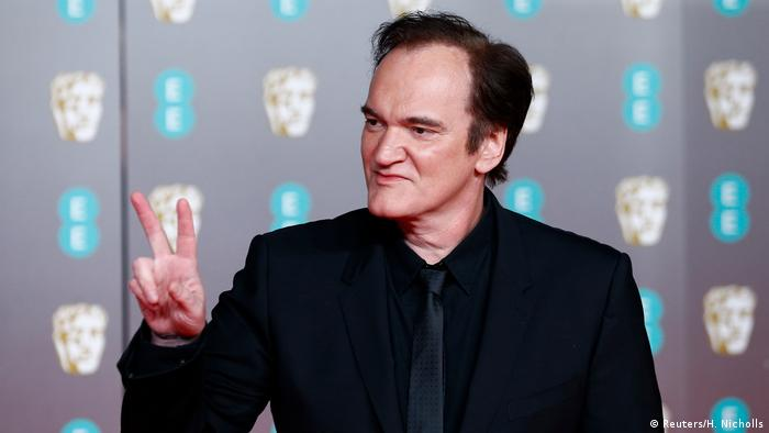 Film director Quentin Tarantino makes a victory sign with his fingers