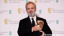 Sam Mendes collects the award for best film at the BAFTAs in a black suit