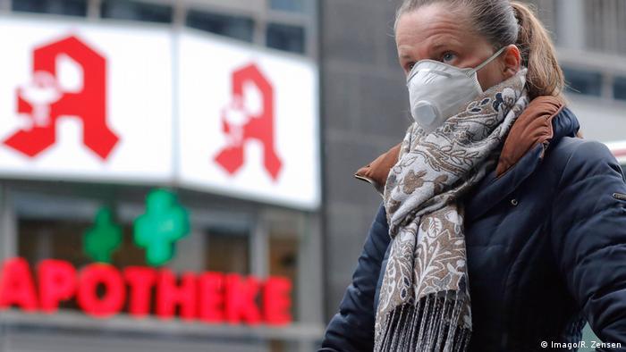 Женщина в защитной маске перед немецкой аптекой